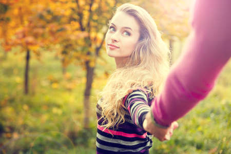 Young Woman Holding Hands on Autumn Background in Sunny Day. Toned Photo with Lens Flare Effect and Copy Space. Stockfoto