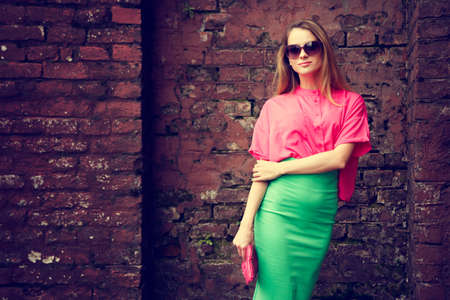 urban fashion: Young Fashionable Woman Standing at the Old Brick Wall Background. Urban Fashion Concept. Toned Photo with Copy Space.