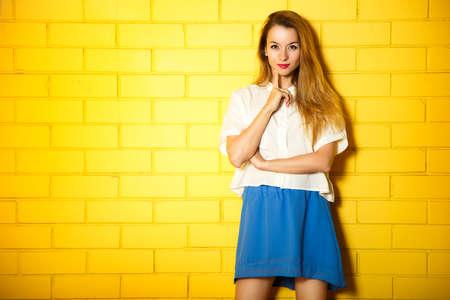 Portret Hipster Dziewczyna na żółty tle ceglanego muru. Miejskie mody pojęcia. Kopiowanie miejsca. Zdjęcie Seryjne