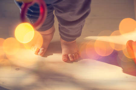 the first step: Small Baby Feet on Wooden Floor. First Steps Concept. Shallow Depth of Field. Toned Photo with Bokeh and Copy Space. Stock Photo