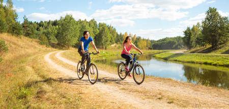 ciclismo: Joven pareja feliz andar en bicicleta por el río. Estilo de vida saludable concepto.