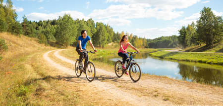 road cycling: Young Happy Couple Riding Bicycles by the River. Healthy Lifestyle Concept.
