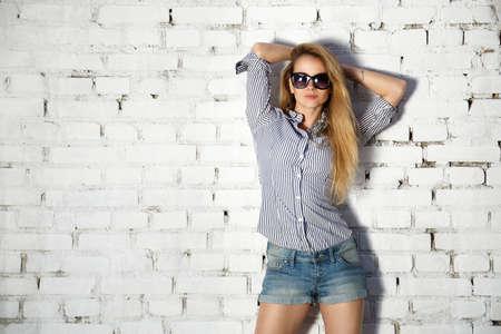 Ritratto di Street Style ragazza teenager con le mani dietro la testa su sfondo bianco muro di mattoni. Moda Trendy Outfit casuale. Archivio Fotografico - 47938677