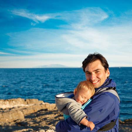 niño con mochila: Padre feliz con su pequeño hijo en Carrier en el fondo del mar. Familia concepto de recreación. Foto cuadrada con espacio de copia. Foto de archivo