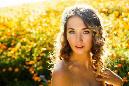 natural beauty: Young Woman with Wedding Hairstyle on Summer Flowers Background. Natural Beauty Concept. Sunshine Backlit Photo Toned in Warm Colors. Stock Photo