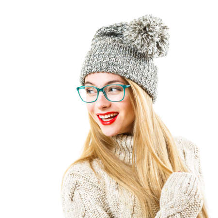 woman  glasses: Smiling Hipster Girl in Knitted Sweater and Beanie Hat Isolated on White. Youth Winter Fashion Concept.