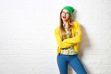 흰색 벽돌 벽 배경에 스트리트 스타일 소식통 소녀입니다. 겨울에 유행 캐주얼 패션 의상. 공간을 복사합니다. 스톡 콘텐츠