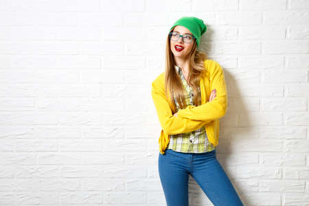 Street Style Hipster Girl at White Brick Wall Background. Trendy Casual Fashion Outfit in Winter. Copy Space. Stok Fotoğraf