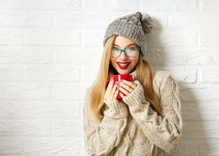 sueter: Sonriendo Hipster Girl in suéter de punto Beanie sombrero y con la taza en las manos en el fondo blanco de la pared de ladrillo. Calentamiento de invierno para arriba el concepto.