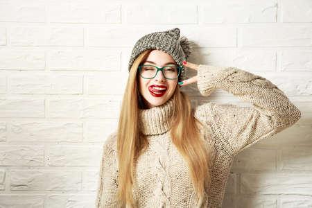 fashion: Funny girl Hipster dans Pull et Bonnet à Going Crazy Fond blanc Mur de briques. Trendy Casual Outfit Mode en hiver. Photo teintée avec Espace texte.
