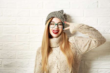 and in winter: Funny Hipster Girl in Knitted Sweater and Beanie Hat Going Crazy at White Brick Wall Background. Trendy Casual Fashion Outfit in Winter. Toned Photo with Copy Space.