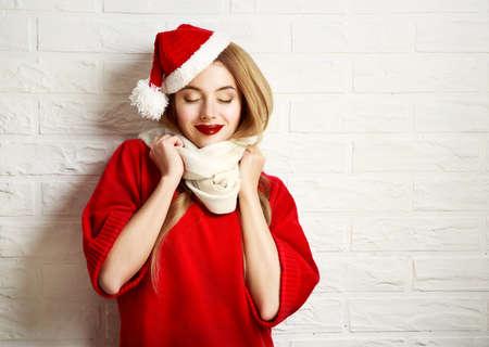 흰색 벽돌 벽 배경에 빨간색 겨울 의류에 닫힌 된 눈을 가진 크리스마스 웃는 소녀. 로맨틱 꿈꾸는 여자의 초상화입니다. 복사 공간 톤의 사진. 스톡 콘텐츠