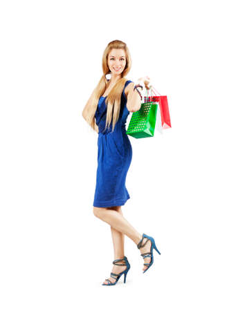 Full Length Portrait of Happy Blonde Woman in Blue Fashion Dress Holding Shopping Bags Isolated on White. Shopping Concept. Stock Photo