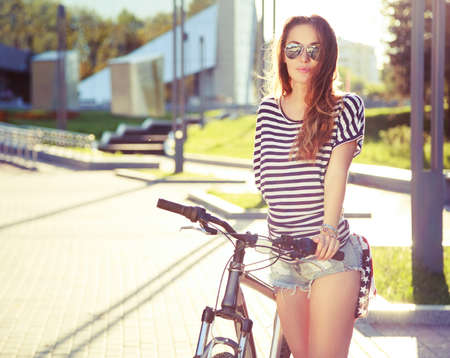 Fashion Hipster Woman with Bicycle in the City. Toned and Filtered Photo. Modern Youth Lifestyle Concept.