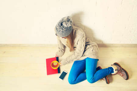 style woman: Young Woman Sitting on the Wooden Floor at Home with a Book, Tea and Smartphone. Modern Youth Mobile Concept. Winter Lifestyle.