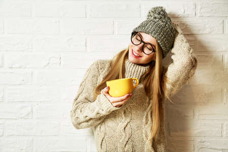 and in winter: Romantic Dreaming Hipster Girl in Knitted Sweater and Beanie Hat with a Mug in Hands at White Brick Wall Background. Winter Warming Up Concept.