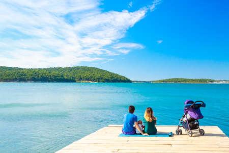 Familie mit wenig Baby sitzt auf einem Pier in der Nähe des Meeres. Sommer-Ferien-und guten Rutsch ins Parenting-Konzept. Kopie Raum.