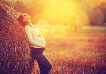 Young Pregnant Woman Standing by the Haystack at Sunset and Embracing her Belly. 7 Month Pregnancy. Happy Maternity Concept. Toned Photo with Bokeh.