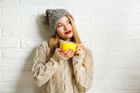 woman sweater: Romantic Dreaming Winter Hipster Girl in Knitted Sweater and Beanie Hat with a Mug in Hands at White Brick Wall Background. Warming Up Concept.