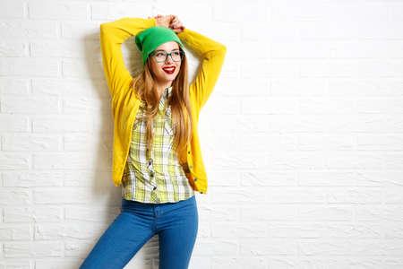 흰색 벽돌 벽 배경에 소식통 웃는 소녀. 거리 Syle. 봄 또는 가을에 유행 캐주얼 패션 의상. 공간을 복사합니다.