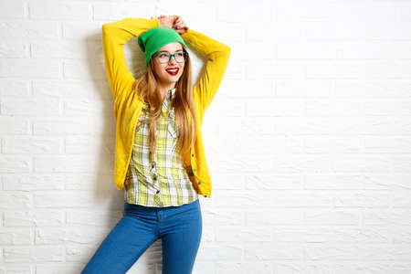 Smiling Hipster Girl at White Brick Wall Background. Street Syle. Trendy Casual Fashion Outfit in Spring or Autumn. Copy Space. Stockfoto