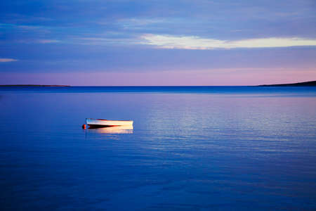 Beautiful Seascape with Lonely White Boat Floating in Blue Sea at Sunset. Peaceful Background with Tranquil Calm Water and Reflection. Copy Space.