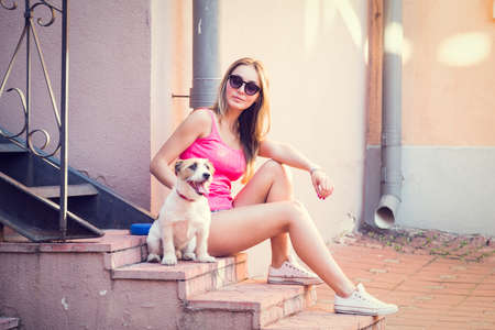 love and friendship: Hipster Fashion Girl with Her Dog on Urban Background. Summer Street Style. Toned and Filtered Photo. Pets Friendly Concept. Stock Photo