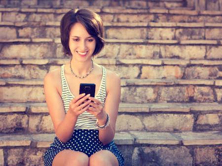 发短信与她的手机的微笑的行家女孩户外。幸福的女人。夏季时尚,青年生活方式,技术和通信概念。与拷贝空间的被定调子的照片。