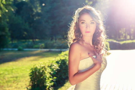 Stylish Young Bride Outdoors Portrait at Green Nature Background. Fahion Wedding Hairstyle and Accessories. Sunset Backlit Light. Toned Photo with Lens Flare Effect.
