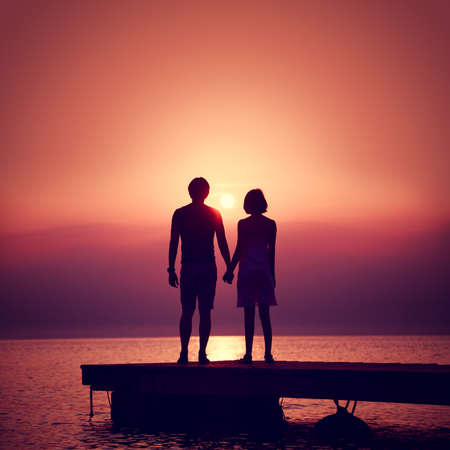 Romantic Couple in Love Holding Hands and Enjoying Sunset at Sea.  Toned and Filtered Square Photo with Copy Space. Man and Woman Relationships Concept.
