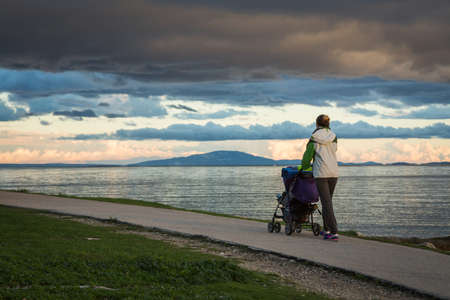 Mother with Baby Stroller Walking by the Sea and Enjoying Beautiful Seascape in Evening. Happy Parenting and Healthy Lifestyle Concept. Copy Space.