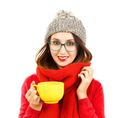beanie: Cute Smiling Hipster Girl in Red Sweater, Scarf and Beanie Hat with Cup in Hands. Portrait Isolated on White. Winter Youth Fashion and Warming Up Concept. Stock Photo