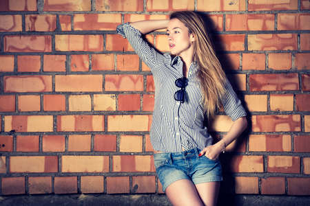 Portrait of Trendy Hipster Girl on Brick Wall Background. Urban Street Style Fashion Concept. Toned Photo with Copy Space. Stock Photo
