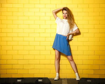 Full Length Portrait of Hipster Fashion Girl Standing at the Yellow Brick Wall Background. Street Style Urban Fashion Concept. Copy Space. photo