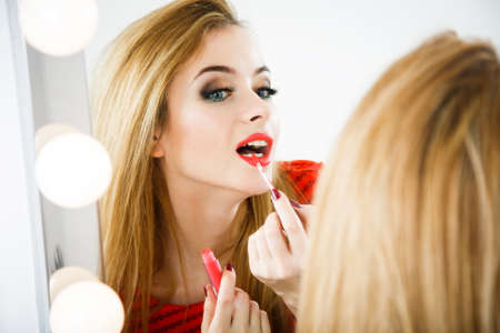 lipgloss: Beautiful Woman Applying Matte Lipstick and Reflected in the Mirror. Fashion Makeup Concept. Stock Photo