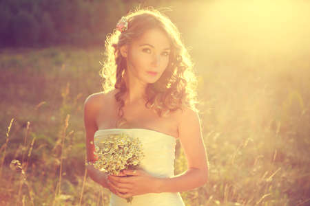 wedding portrait: Stylish Young Bride Outdoors Portrait at Nature Background. Fahion Wedding Hairstyle and Accessories. Sunset Backlit Light. Toned Cross Processed Photo with Soft Focus.