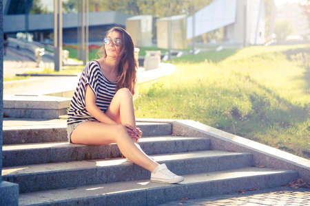 Hipster Street Style Fashion Girl Relaxing in the City. Summer Sunlight Background. Toned and Filtered Photo. Free Youth Lifestyle Concept.