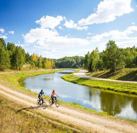 강에 의해 젊은 행복 부부를 타고 자전거. 아름다운 자연 배경입니다. 야외 스포츠와 건강한 라이프 스타일 개념입니다. 공간을 복사합니다.
