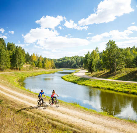 Feliz jóvenes bicicletas Pareja a caballo por el río. Hermoso fondo de la naturaleza. Deporte al aire libre y concepto estilo de vida saludable. Espacio en blanco.