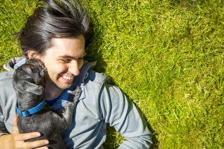 amigos abrazandose: Poco perro y su due�o feliz que se divierten y acostado en la hierba verde. Amor y animales dom�sticos que juegan Concepto. Espacio en blanco.