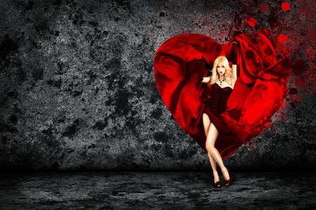 Tanzen Frau mit Spritzen Seidenkleid in Herzform. Dark Concrete Wall Background als Textfreiraum. Liebe Konzept für den Valentinstag. Standard-Bild