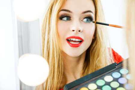 blond girl: Beautiful Woman Applying Eyeshadow Makeup and Reflected in the Mirror. Fashion Makeup Concept.