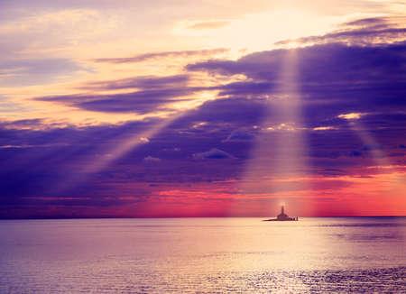 cielo con nubes: Faro en la puesta del sol. Hermoso mar y el cielo de fondo dramático nubes con rayos de sol. Concepto náutica. La foto en tonos Espacio en blanco. Foto de archivo