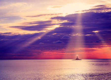 sunset clouds: Lighthouse at Sunset. Beautiful Sea and Dramatic Sky Clouds Background with Sunrays. Nautical Concept. Toned Photo with Copy Space. Stock Photo