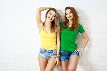 Two Sexy Smiling Hipster Girls Posing at White Brick Wall Background. Trendy Casual Fashion Outfit in Summer. Youth Friendship and Lifestyle Concept. Toned Photo with Copy Space.