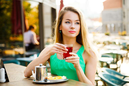 Beautiful Woman Drinking Tea in a Cafe Outdoors. Summer City Background. Shallow Depth of Field. Toned Photo. photo
