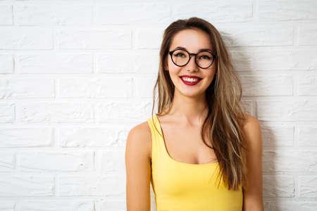 Happy Smiling Hipster dziewczyna w okulary na biały tle ceglanego muru. Ulica Lato Style Moda Outfit. Kopia przestrzeń.