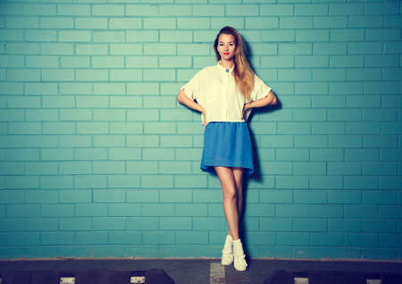 Full Length Portrait of Trendy Hipster Girl Standing at the Turquoise Brick Wall Background. Urban Fashion Concept. Toned Photo with Copy Space. photo