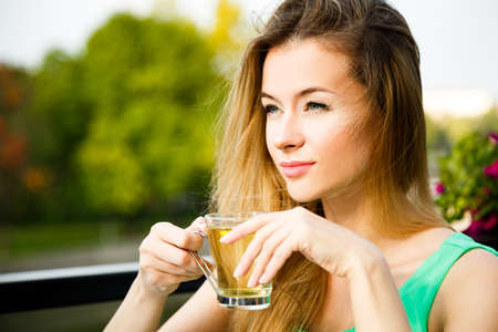 Dreaming Young Woman Drinking Green Tea Outdoors. Summer Green Nature Background. Shallow Depth of Field. photo