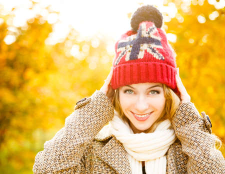 Happy Woman in Beanie Hat on Autumn Background in Sunny Day. Smiling Happy Girl Portrait. Toned Photo with Copy Space.